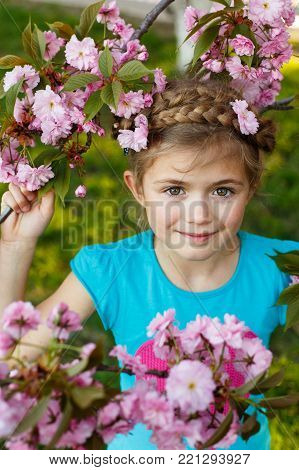 Adorable young girl having fun in blossom cherry garden on beautiful spring day. Little cute child walking on family holidays. Beautiful toddler kid play in park