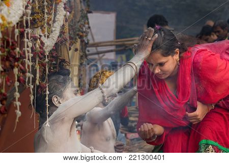 BABUGHAT, KOLKATA, WEST BENGAL / INDIA - 11TH JANUARY 2015 : Hindu Sadhu with white ash applied on body and face, blessing red coloured dress clad Indian devotee woman.