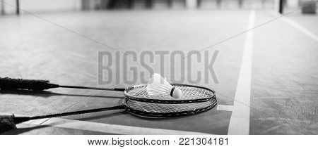 Badminton ball (shuttlecock) and racket on court floor. Black and white banner panoramic crop for copy space. Badminton ball sunset. Badminton ball and racket. Badminton ball sunlight.
