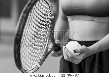 Player's hand with tennis ball preparing to serve in court. black and white. tennis on sunset. tennis sport girl. tennis racket. tennis player