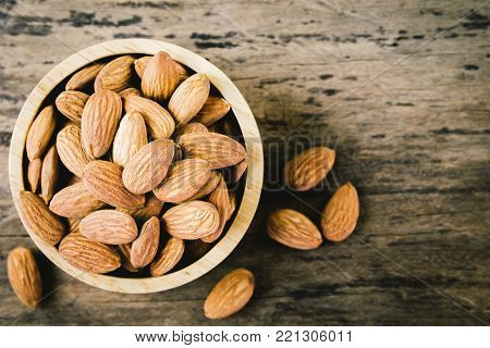 Almonds in brown bowl on textured wooden background, top view. vintage tone. Close up almond background.  almonds for texture.