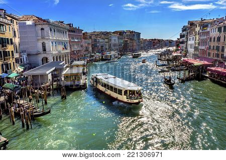 VENICE, iTALY - SEPTEMBER 21, 2017 Colorful Grand Canal Public Ferries Vaporetto Ferry Docks Gondola From Rialto Bridge Touirists Grand Canal Venice Italy