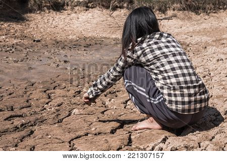 The woman sat on a barren ground with despair.