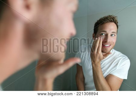 Face cream young man putting skincare beauty product on face hydrating skin. Male beauty facial treatment care at home lifestyle. Person applying moisturizer for dry skin during winter.