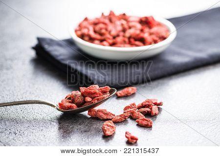 Dried goji berries in spoon.