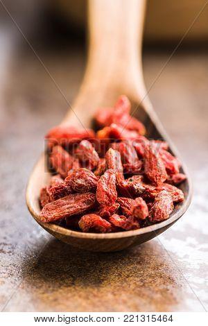Dried goji berries in wooden spoon.