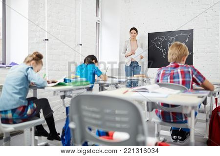 Group of schoolkids making notes after teacher at lecture