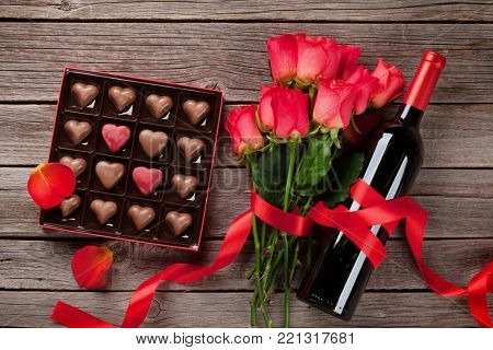 Valentines day greeting card with red roses and heart shaped chocolate and wine bottle on wooden background. Top view
