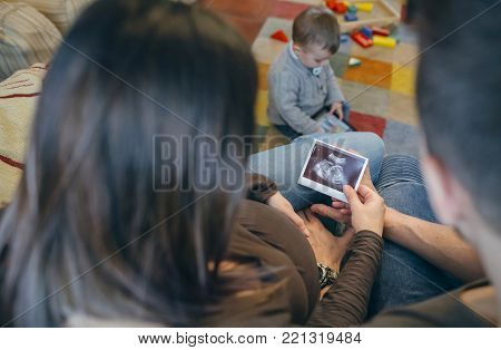 Parents looking at the ultrasound of their new baby while the older brother plays