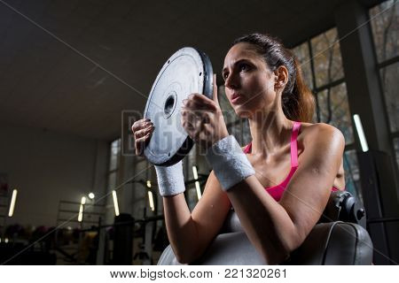 Strong active female with barbell plate lifting it during training in gym