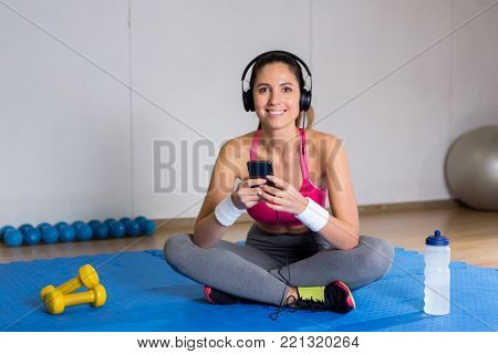 Happy young woman with headphones and smartphone listening to music while sitting on mat