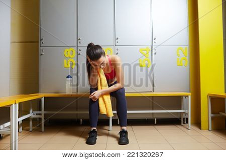 Exhausted young woman sitting on bench in changing room after training