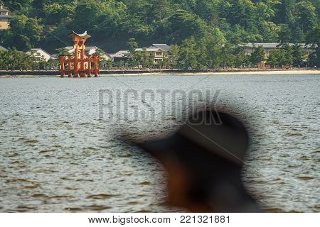 Long shot in Miyajima with Floating Torii gate and tourist head in the blurred foreground, Japan.