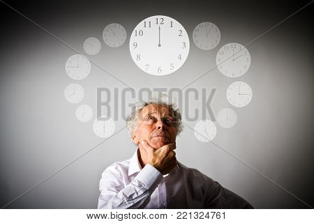 Old man in white is full of doubts and hesitation. Time and day concept. Time is passing.