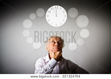 Old man in white is full of doubts and hesitation. Three Minutes to Twelve. Time and day concept. Time is passing.