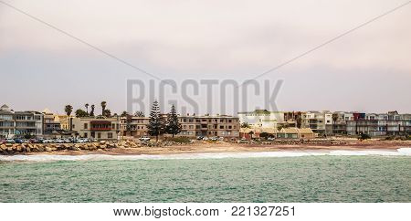 Сoastline panorama with houses in background, Swakopmund German colonial town, Namibia