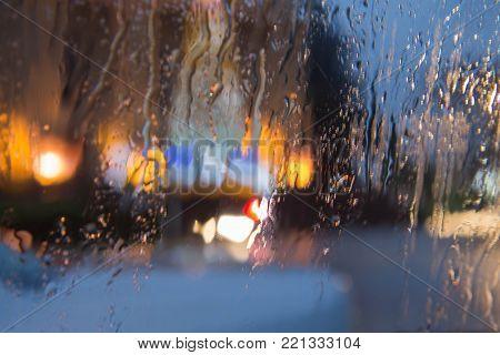 Rainy days,Rain drops on window,rainy weather,rain background,rain and bokeh. Blurry Building silhouette