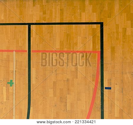 Wooden floor in sporting hall with solid and dotted lines.  Light reflection in polished wooden floor with colorful marking lines