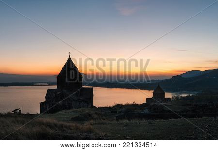 Panoramic view of the temple complex on the Sevan Lake at sunset, Armenia. Silhouettes of St. Jakob Church and Sevanavank. Armenian landmarks