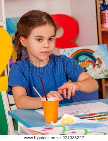 Small students painting in art school class. Child drawing by paints on table in kindergarten. Newcomer in a children's team. Girl dreams of spring and summer.