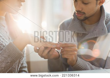 Amorous guy putting engagement ring on his girlfriend finger after making proposal