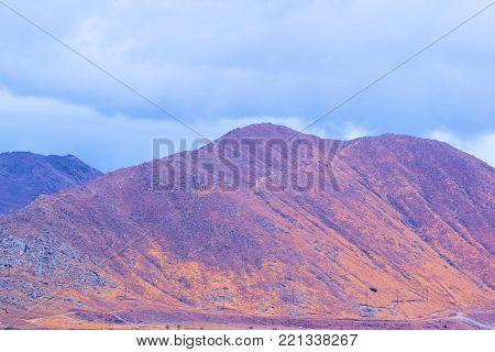 Storm clouds over rural, arid, and golden hills taken in Riverside, CA