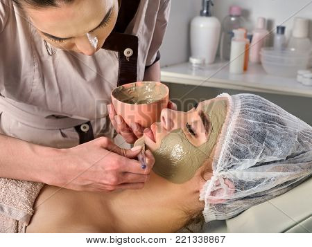 Mud facial mask of woman in spa salon. Massage with clay full face. Girl on with therapy room. Female lying wooden spa bed. Beautician with bowl therapeutic procedure isolated background. Best clinics