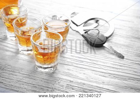 Glasses of alcohol with handcuffs and car key on wooden table. Don't drink and drive concept