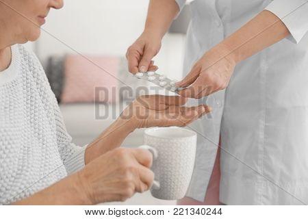 Caregiver giving medicine to senior woman at home, closeup