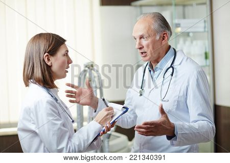 Two professional doctors in whitecoats discussing new medicine in hospital