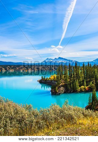 Magnificent turquoise Abraham Lake. In the blue sky silver trace of the plane. Rocky Mountains of Canada in the Indian summer. The concept of ecological and active tourism