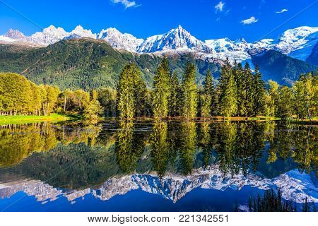 Fantastic sunset in the Alps. Concept of active and ecotourism. Snowy peaks of the Alps are reflected in the lake in mountain resort of Chamonix. The foot of Mont Blanc