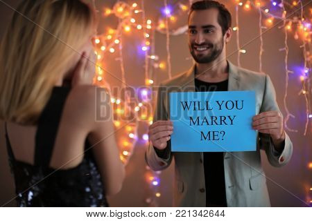 Young man holding paper with text WILL YOU MARRY ME? in front of his girlfriend on engagement day