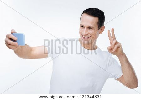 My photo. Nice positive good looking man holding his smartphone and showing V sign while taking selfie