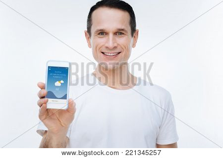 Weather forecast app. Cheerful positive nice man smiling and showing his smartphone while looking at you