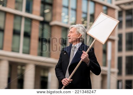 Senior businessman taking part in demonstration with placard in urban environment