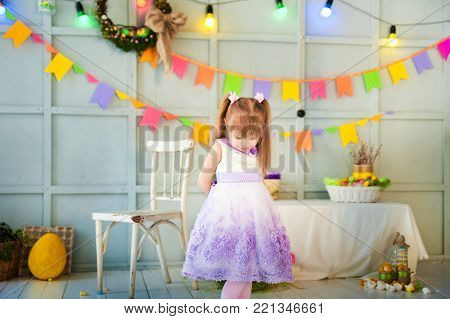 A little girl is standing in a decorated room, and downtrodden or punished her head, looking at the floor. Easter photo with a garland, eggs, a hare, a child.