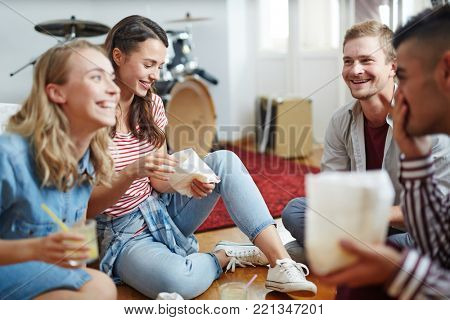 Happy friends with snacks and drinks sitting on the floor and having talk