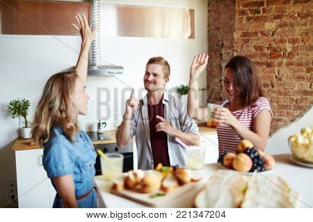Young dancing friends with drinks having home party in the kitchen
