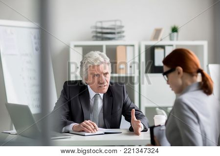 Dissatisfied boss scolding one of his subordinates during meeting in his office