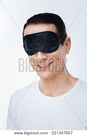 Time to rest. Positive nice delighted wearing a sleeping mask and being ready to sleep while standing against white background