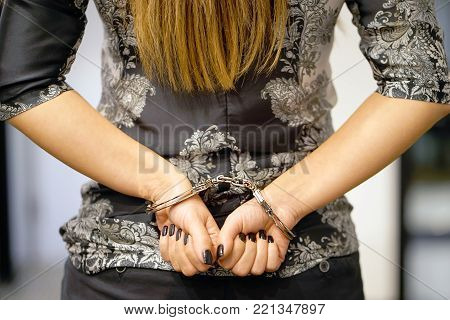 Close-up. Arrested woman handcuffed hands at the back. Prisoner or arrested terrorist, hacker, bribetaker, close-up of hands in handcuff.