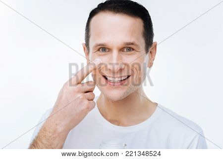 Handsome face. Portrait of a delighted nice handsome man smiling and looking at you while putting on facial cream