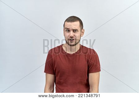 Portrait of funny man with a discouraged shocked surprised look, raising one eyebrow and opening his mouth from the overflowing emotions.
