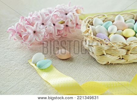 Spring Composition of Easter eggs in basket with yellow ribbon and fresh bud of pink hyacinth copy space Preparation for Spring Easter decoration