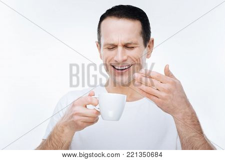 Wonderful aroma. Nice pleasant handsome man holding a cup of coffee and smelling its aroma while standing against white background