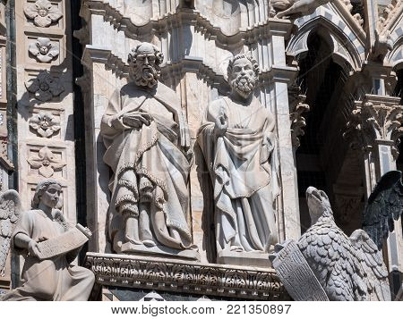 Statues of philosophers and an eagle on the west facade of Siena cathedral