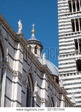 Exterior of Siena Cathedral with scupltutes of philosophers and golden cross on cupola next to the bell tower