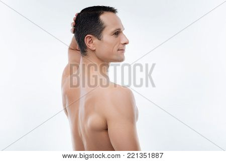 Perfect body. Nice pleasant handsome man standing half face and looking in front of him while touching his head