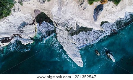 Aerial view of landmark big white chalk rock at Governor's beach, Limassol, Cyprus. The steep stone cliffs and deep blue sea waves crushing in coves and dark sand from above.